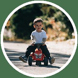 enfant sur un jouet roulant rouge