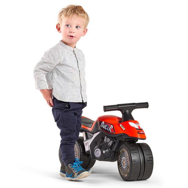 Kleiner spielender Junge mit Laufrad Motorrad Dakar 406D
