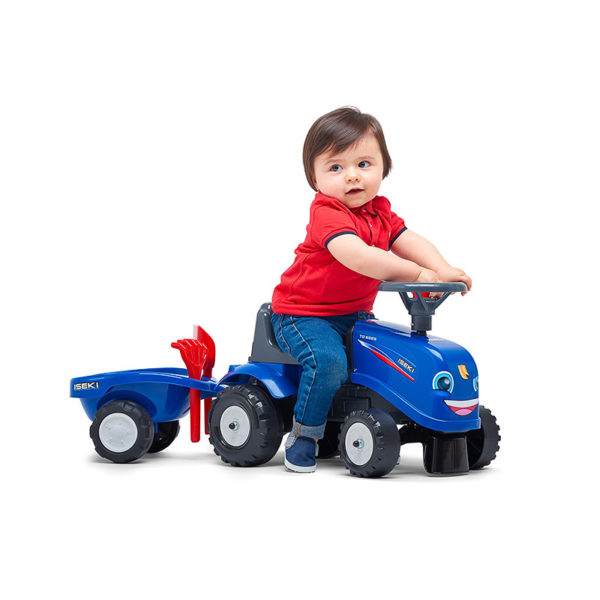 Child playing with New Holland 422 motorcycle balance bike