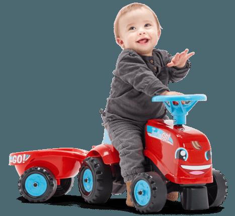 petit enfant souriant sur un tracteur Falk Toys