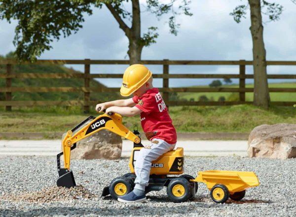 Niño jugando con excavadora JCB 115A en el aire libre