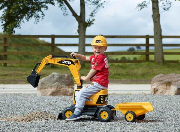 Niño jugano con excavadora JCB 115A en el aire libre