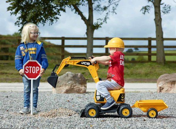 Niño jugano con excavadora JCB Falk Toys 115A en aire  libre