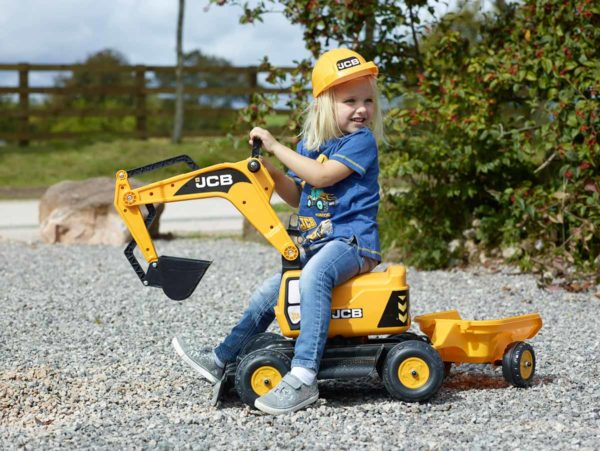 Little girl playing with backhoe JCB 115A outdoors