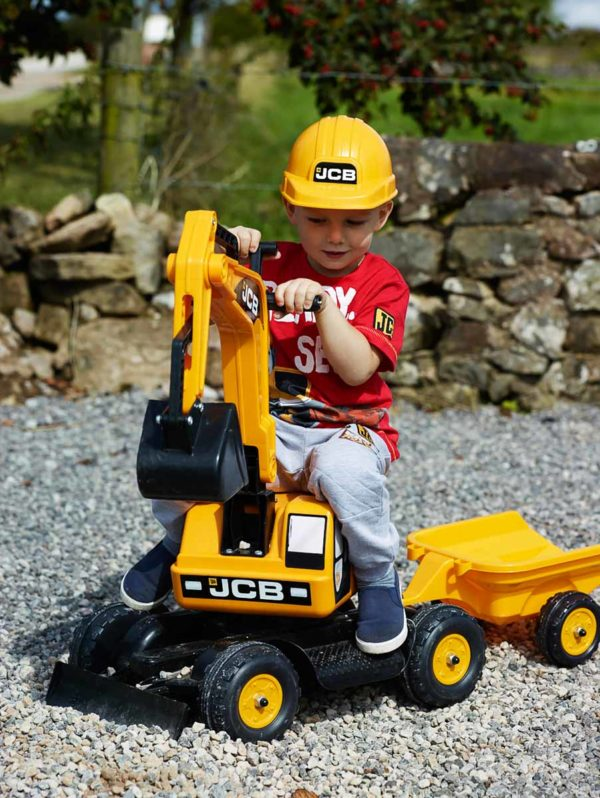 Boy on an outdoor toy JCB 115A