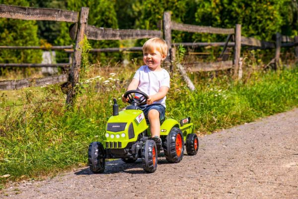 Child playing with Claas 2041C Pedal tractor outdoors