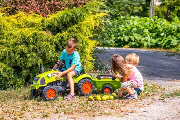 Child playing with Falk Toys Claas 2041C Pedal tractor outdoors