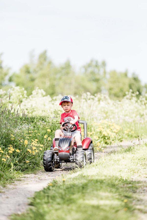 Niño jugando con Tractor Valtra de pedal 4000AB en aire libre