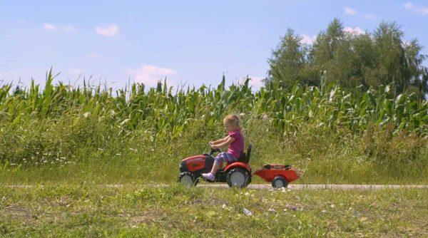 Spielendes Kind mit Traktor Case IH 961B im Freien