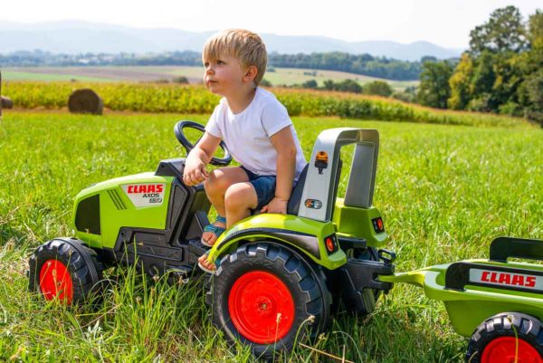 Child playing with Claas 1011AB Pedal tractor outdoors
