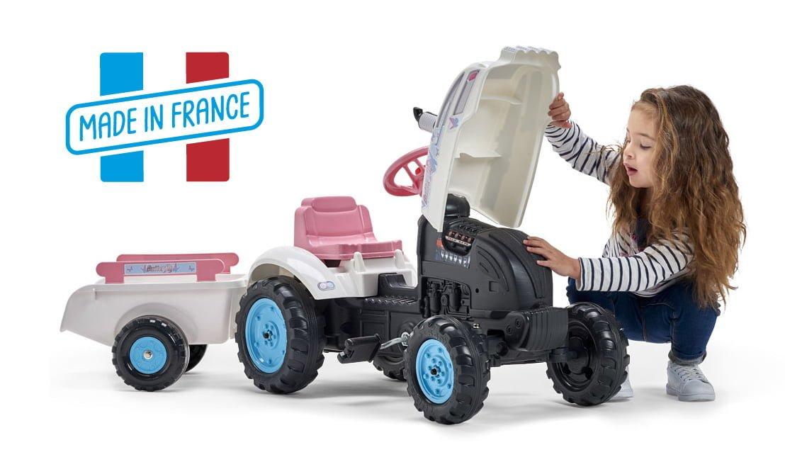 petite fille soulevant le capot de son tracteur rose