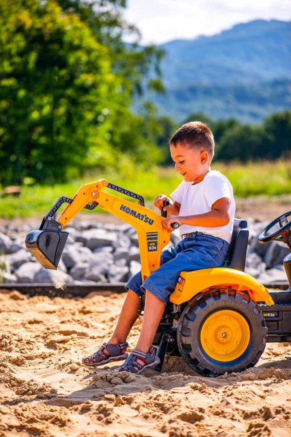 Child playing with Komatsu 2086N pedal backhoe loader outdoors
