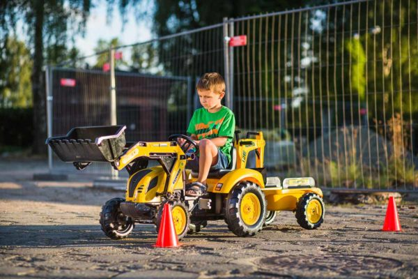 Child playing with Komatsu 2086Y pedal backhoe loader outdoors