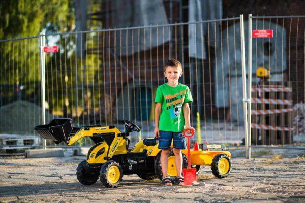 Petit garçon jouant avec Tractopelle à pédales Komatsu Falk Toys 2086Y en plein air