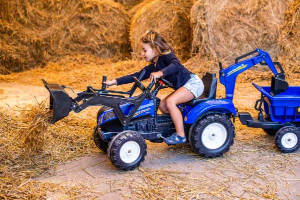 Little girl playing with Falk Toys New Holland 3090W Backhoe outdoors