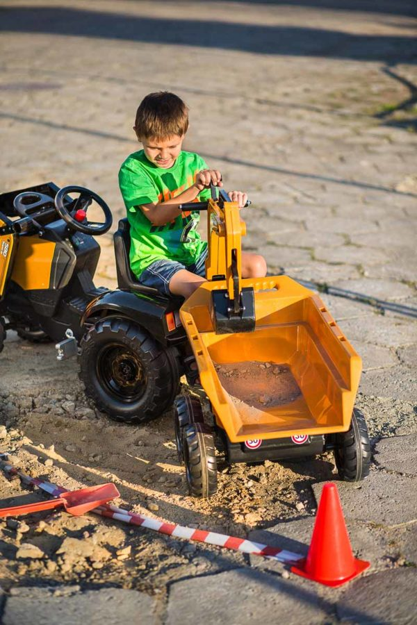 Child playing with trailer of the Case Construction 997W backhoe loader outdoors