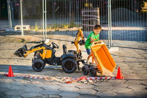 Child playing with trailer of Falk Toys Case Construction 997W backhoe loader outdoors